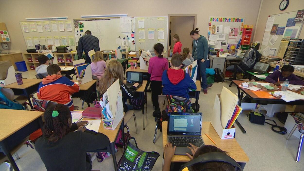 Une salle de classe avec plusieurs élèves du primaire assis à leur bureau.