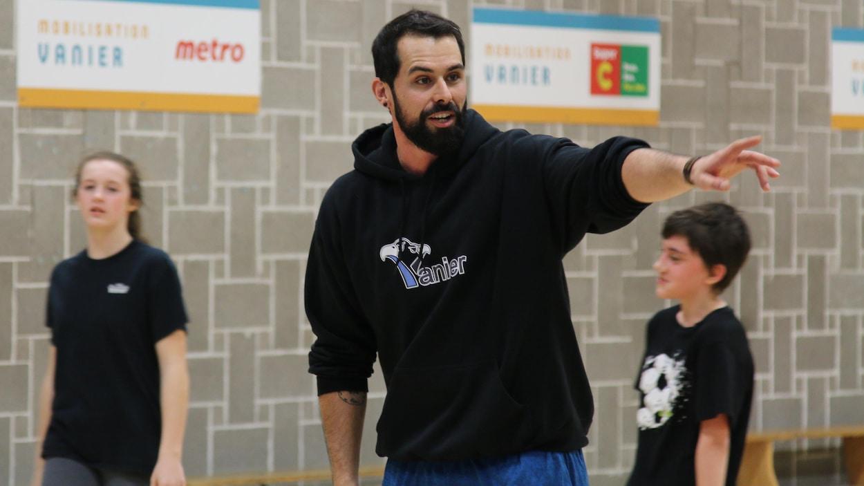 Nicolas Roy donne des instructions à des élèves qui font du sport dans un gymnase.