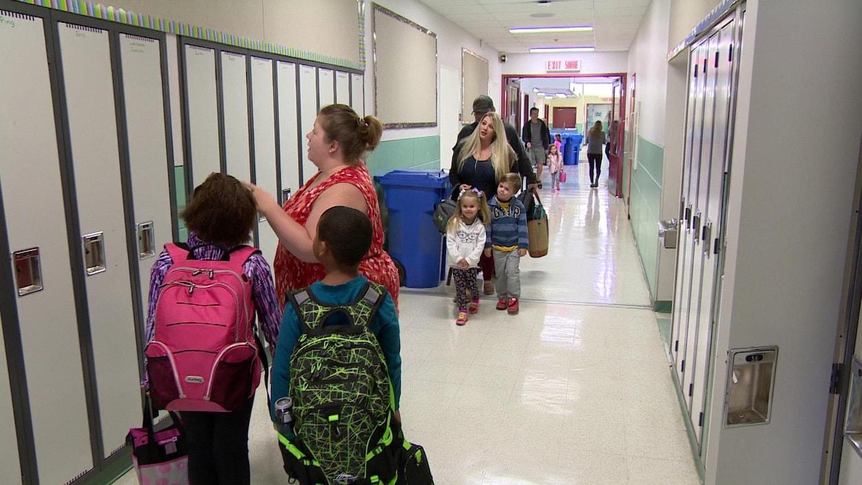 Une enseignante montre un casier à deux jeunes élèves, alors que des parents accompagnent leurs enfants à leur classe.