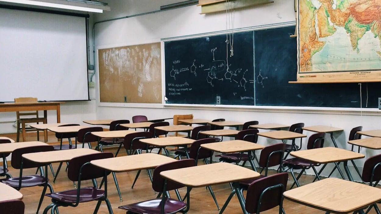 Une salle de classe vide avec un tableau, des tables et des chaises.
