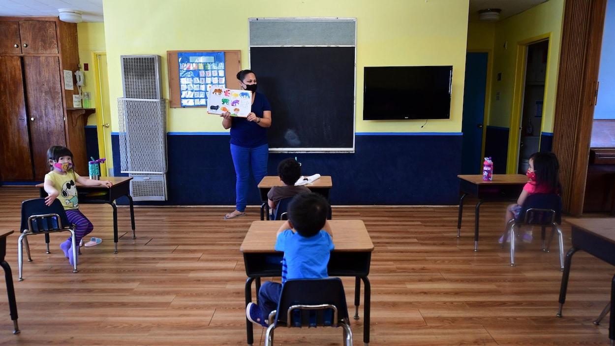 De jeunes élèves assis dans une salle de classe. Les pupitres sont positionnés à deux mètres de distance les uns des autres.