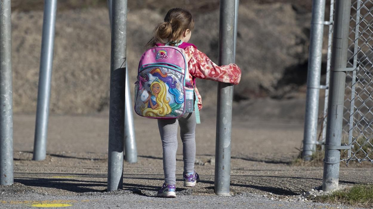 Une petite fille, de dos, portant un sac d'école.