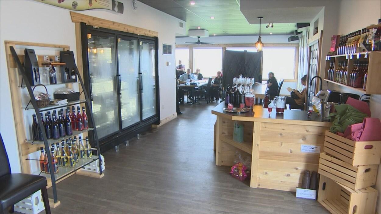 Vue de l'intérieur de l'économusée avec en avant-plan un bar et en arrière plan des personnes assises à table.