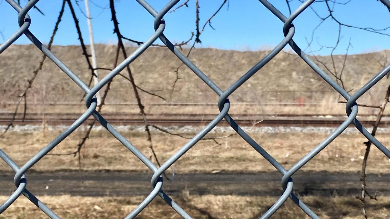 Le terrain contaminé appartenant à Ray-Mont Logistiques vu de l'autre côté d'une clôture de broche.