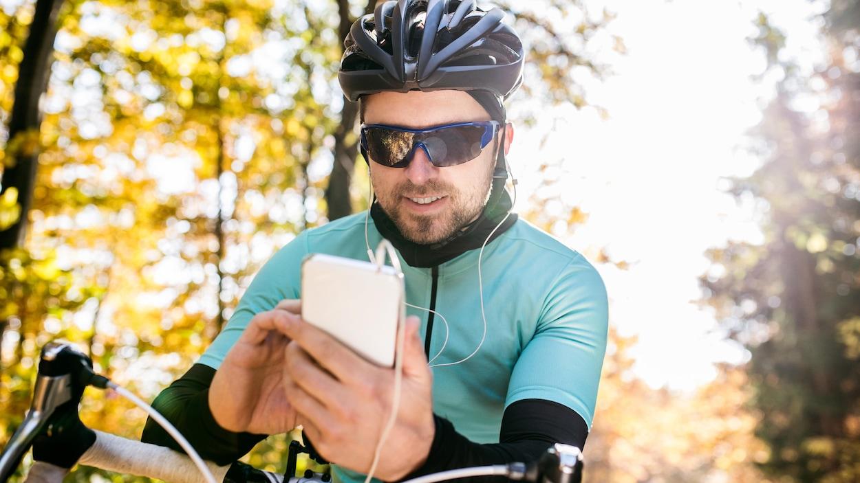 Un cycliste utilise son téléphone portable alors qu'il se trouve sur sa bicyclette. Il porte également des écouteurs.