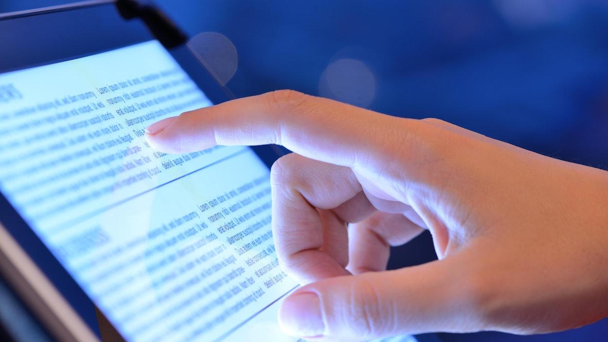 Un doigt pointe un article affiché sur l'écran d'une tablette.