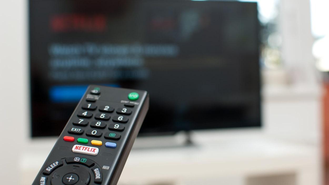 Une télécommande avec un bouton Netflix pointe vers un écran de télévision.