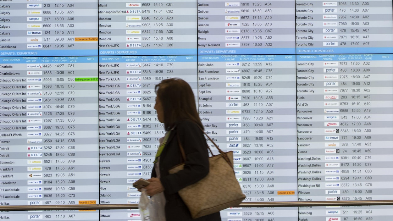 Des écrans indiquant le statut des arrivées et des départs, à l'aéroport Pierre-Elliott-Trudeau, à Montréal.
