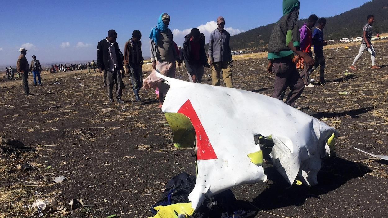 Une dizaine de personnes passent à côté d'un morceau de la carlingue de l'avion.