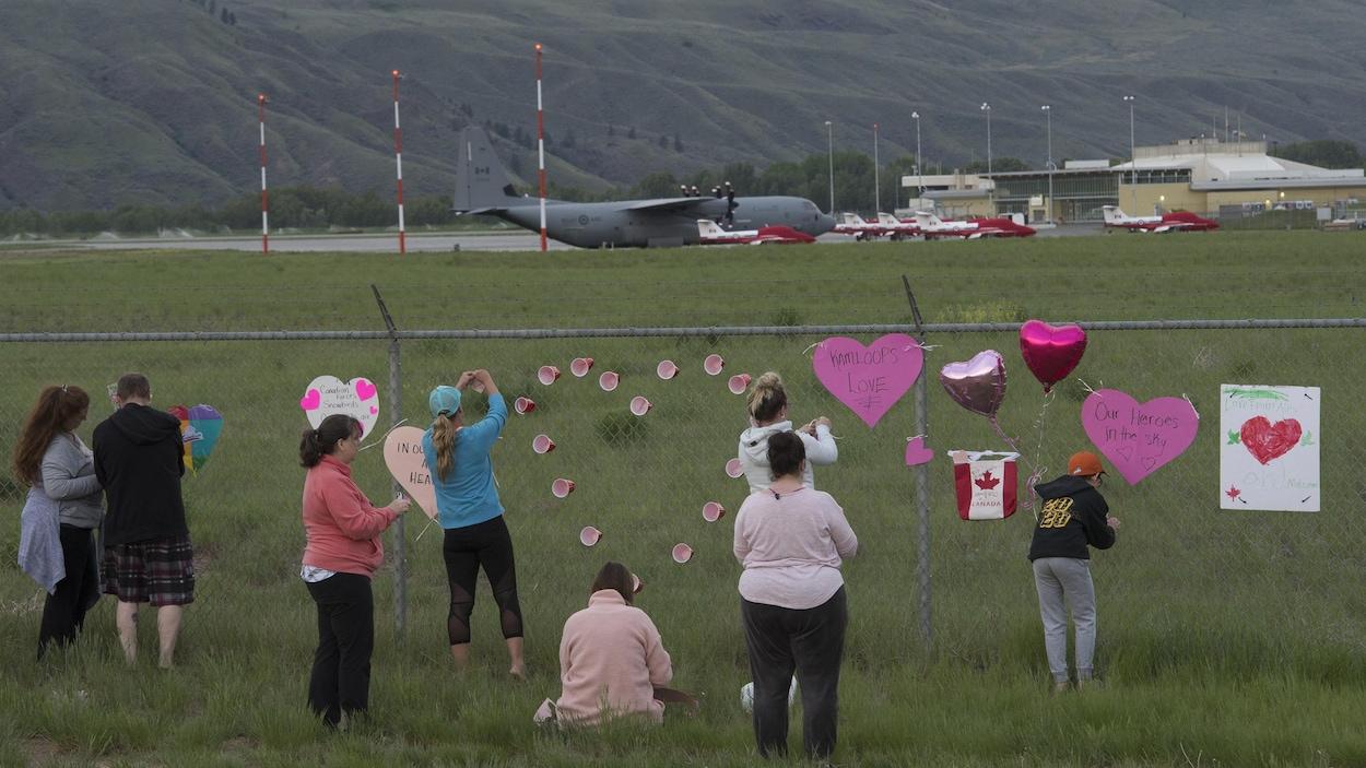 Des personnes accrochent des cœurs sur la clôture d'un aéroport.