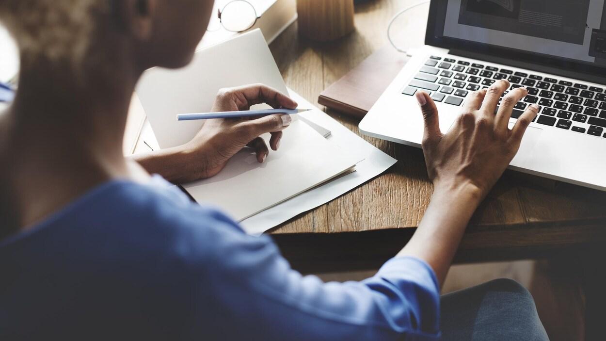 Une femme écrit à l'ordinateur et a aussi un stylo dans la main.