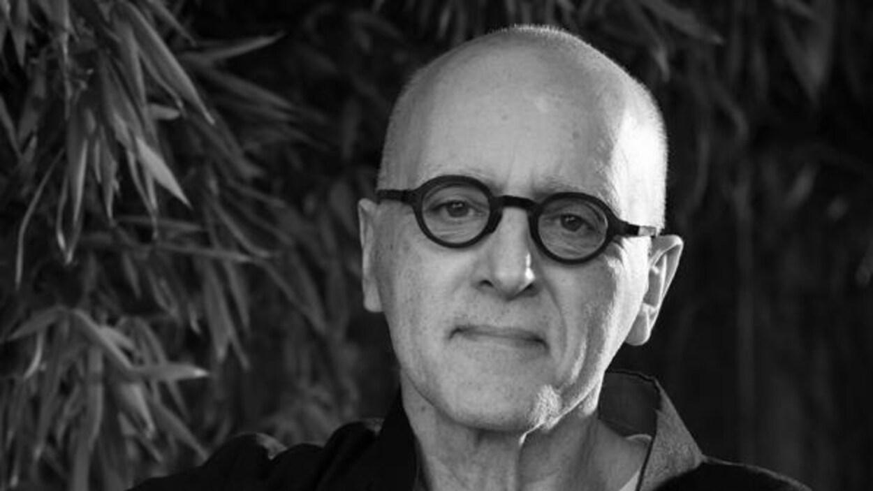 Sur une photo en noir et blanc, un homme, chauve, porte des lunettes rondes.