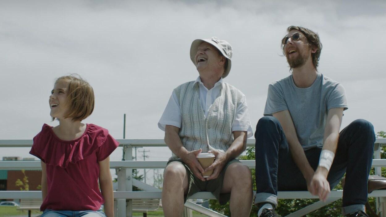 Trois personnage de la série  Écrivain public  sont assis dans des estrades en regardant le ciel, ébaubis.