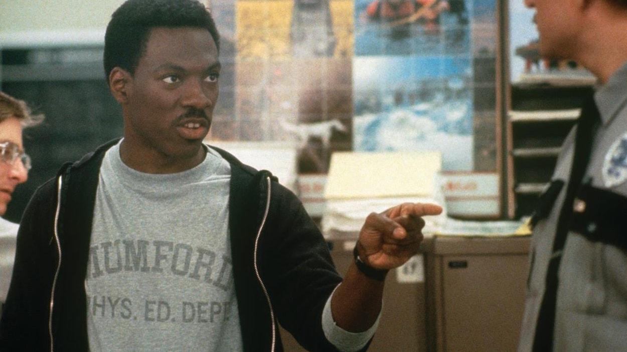 Dans une scène de film, un Eddie Murphy plus jeune montre un policier du doigt en lui parlant.