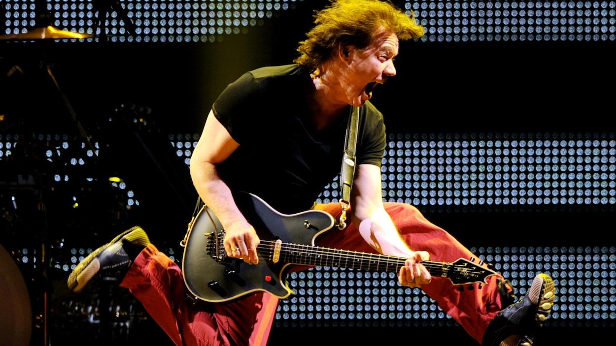 L'homme joue de la guitare en sautant en l'air.