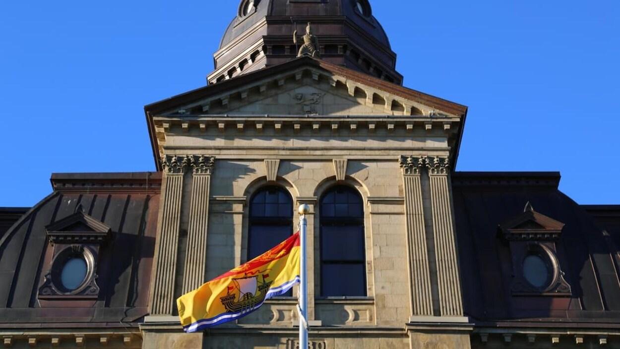 Le drapeau du Nouveau-Brunswick flotte devant l'édifice de l'Assemblée législative