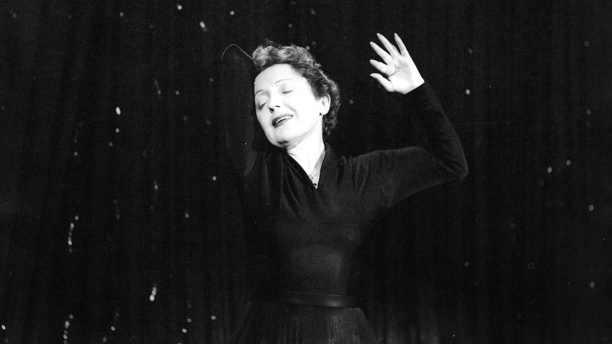 La chanteuse Édith Piaf, en performance, les yeux fermés dans une pose dramatique.