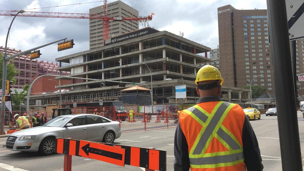 Un travailleur regarde un chantier de construction au centre-ville d'Edmononton.