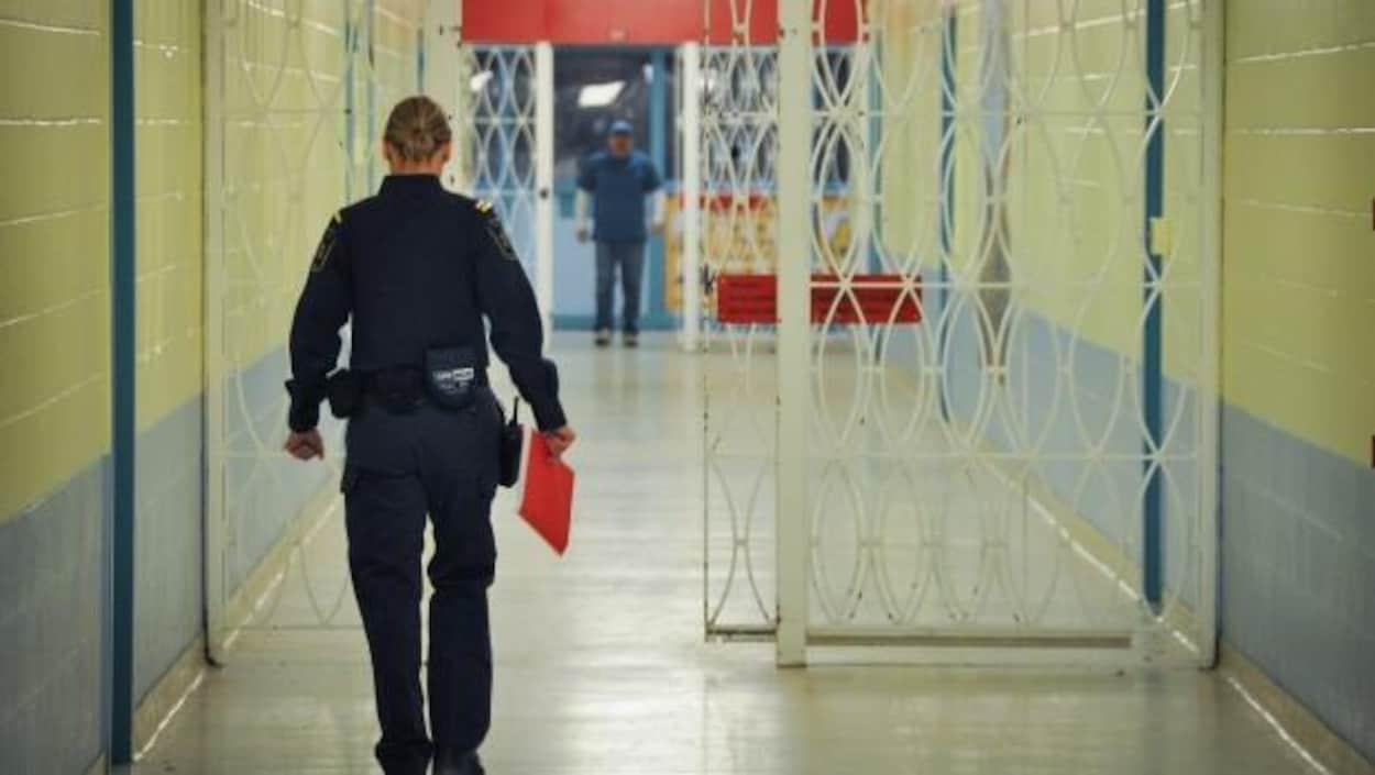 Une agente de services correctionnels marche dans le couloir d'une prison.