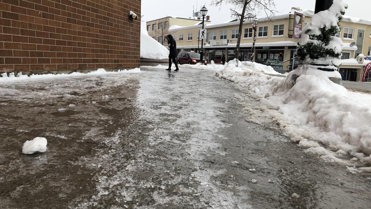 Une femme marche difficilement sur un trottoir recouvert de verglas