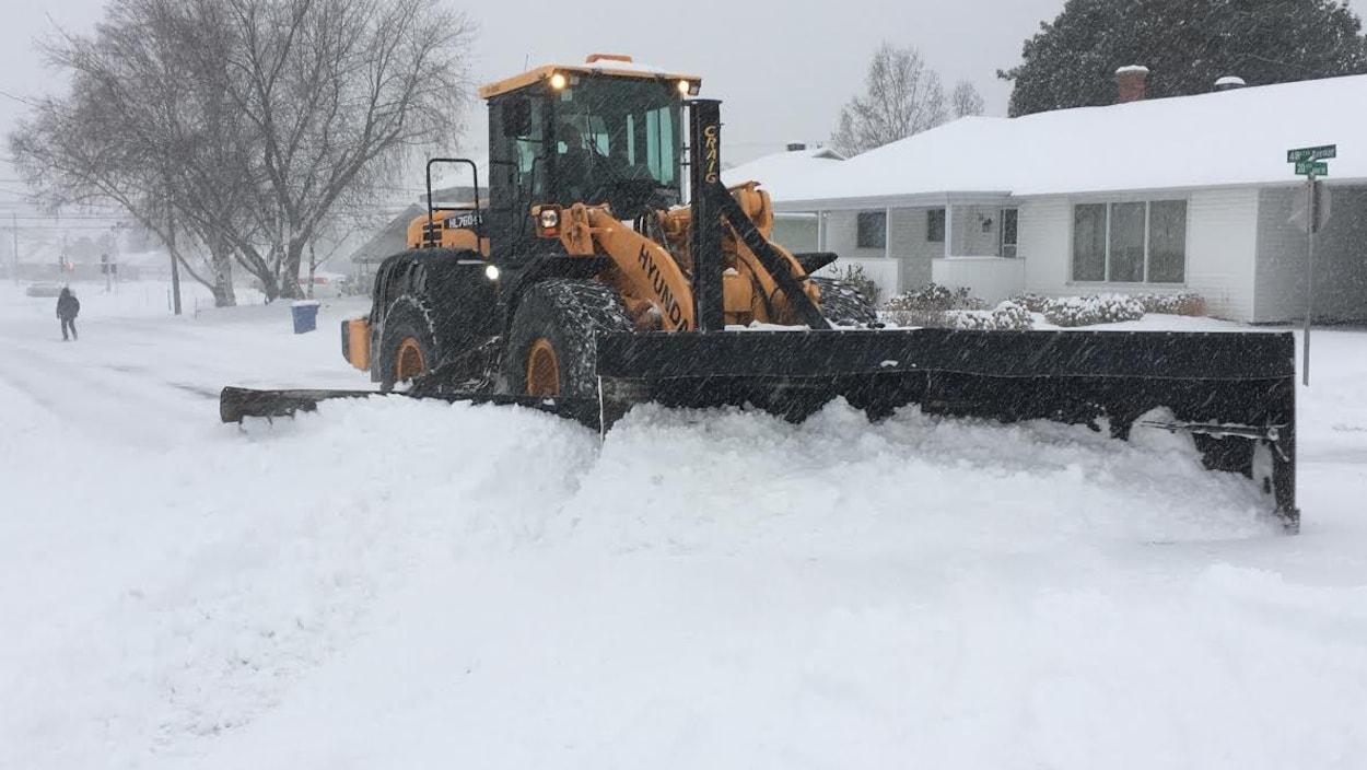 Un chasse-neige dégage une rue.