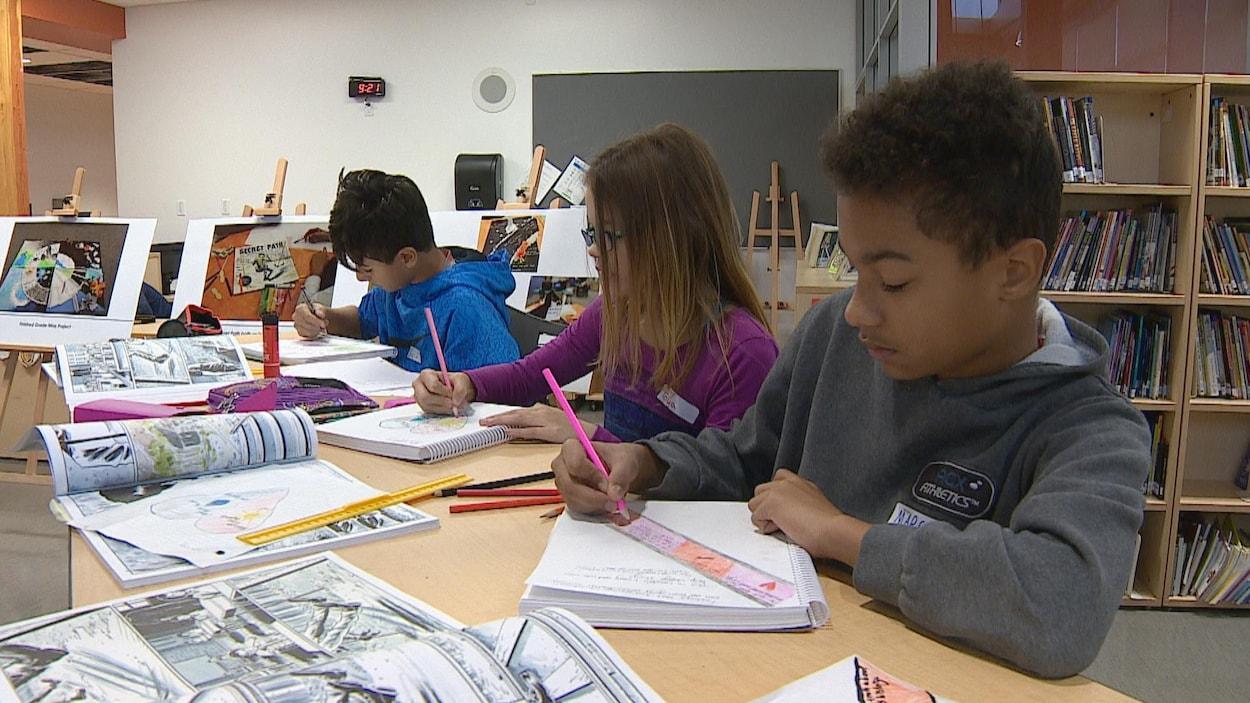 Trois enfants écrivent dans des cahiers, entourés de ressources pédagogiques.