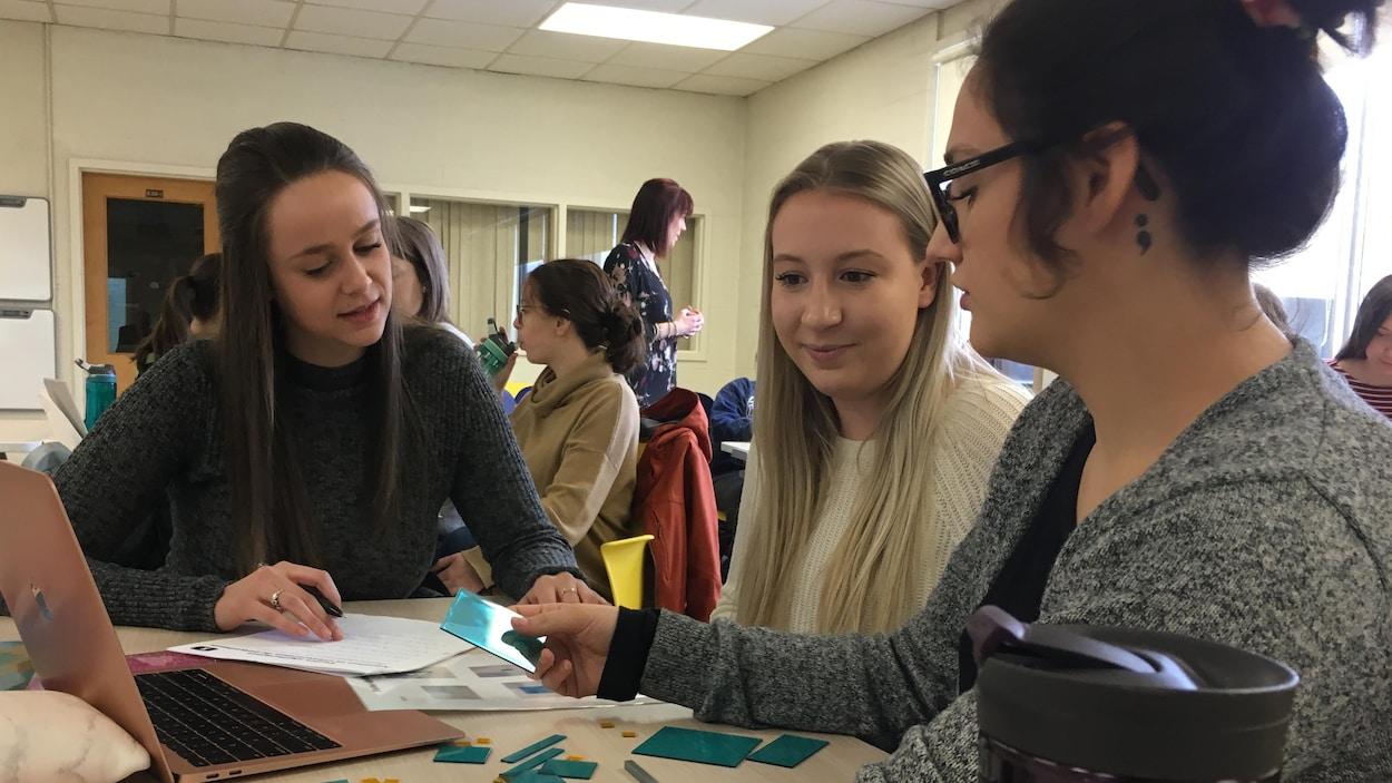 Trois étudiantes discutent autour d'une table dans une classe.