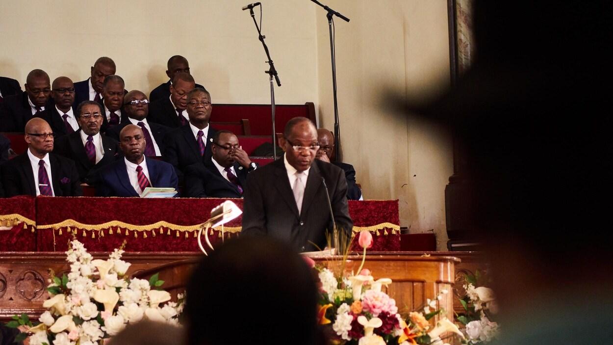 On voit de face un homme parler aux fidèles réunis dans l'église. En arrière-plan, une dizaine d'hommes sont assis et écoutent l'orateur.