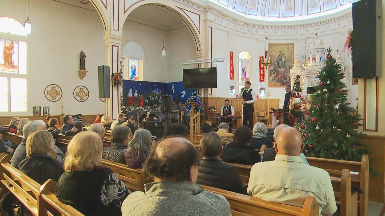 Gens assis dans l'église avec un chanteur et un sapin de Noël.