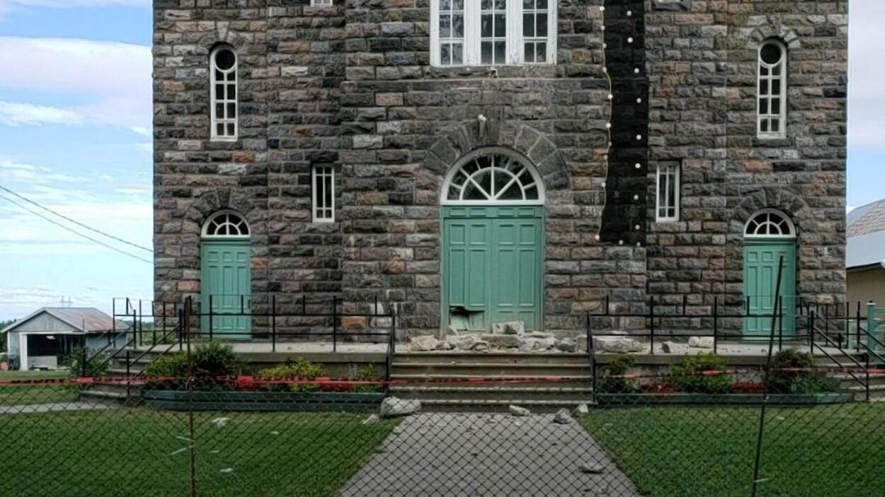 Un périmètre de sécurité est érigé autour de l'église. De grosses pierres sont éparpillées sur le parvis de l'église.