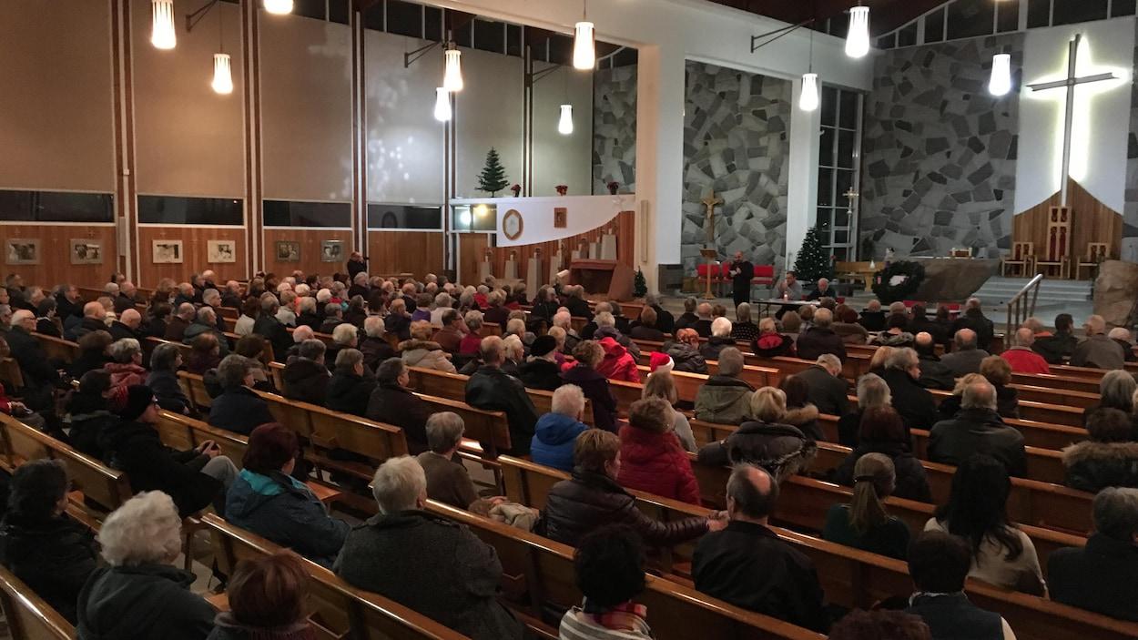 De nombreuses personnes sont assises dans les bancs de l'église Saint-Pie-X à Rimouski.