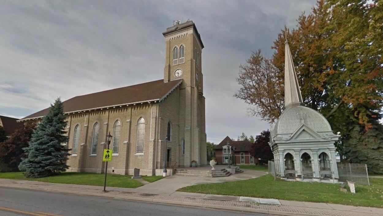 Un église, son clocher est installé devant sur la pelouse