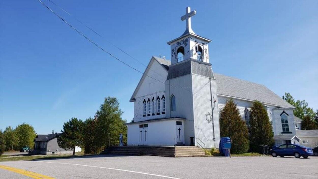 Une église blanche se dresse sous un ciel bleu.