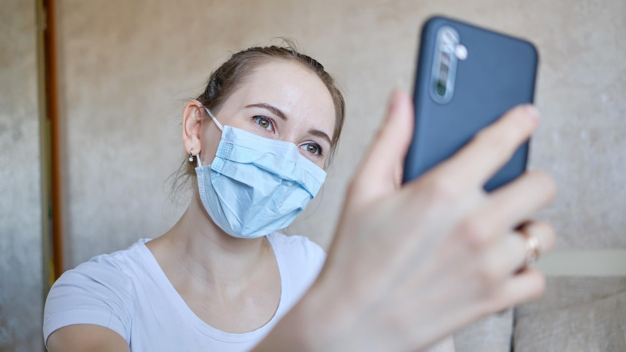 Une femme portant un masque hygiénique prend un égoportrait.