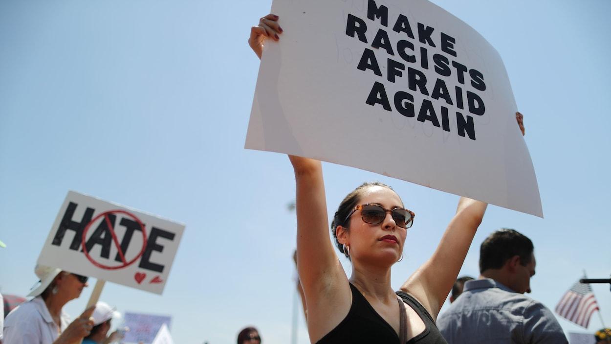 Une femme tient une affiche sur laquelle est écrit : « Make racists afraid again ».