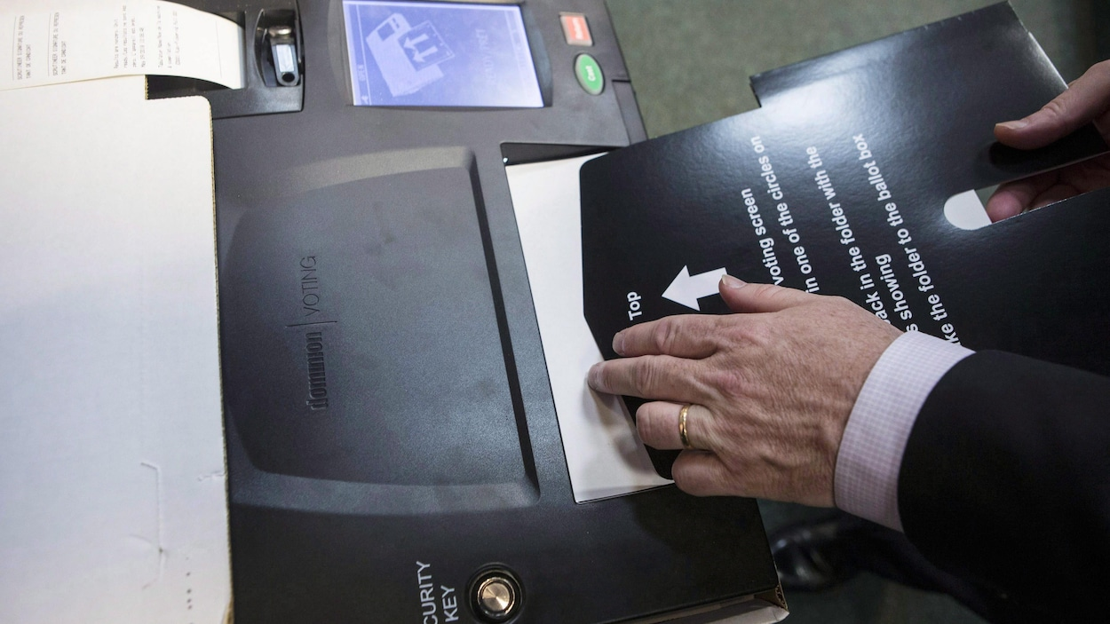 Ontario's Chief Electoral Officer Greg Essensa slides a ballot into a vote tabulator as he demonstrates an electronic voting machine during a media availability in Toronto on Wednesday, May 9 , 2018. THE CANADIAN PRESS/Chris Young