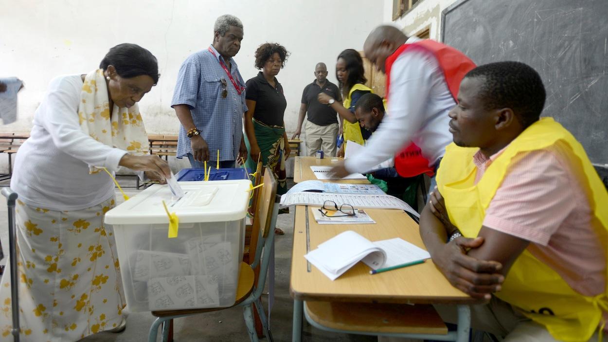 Des femmes et des hommes dans un bureau de vote.