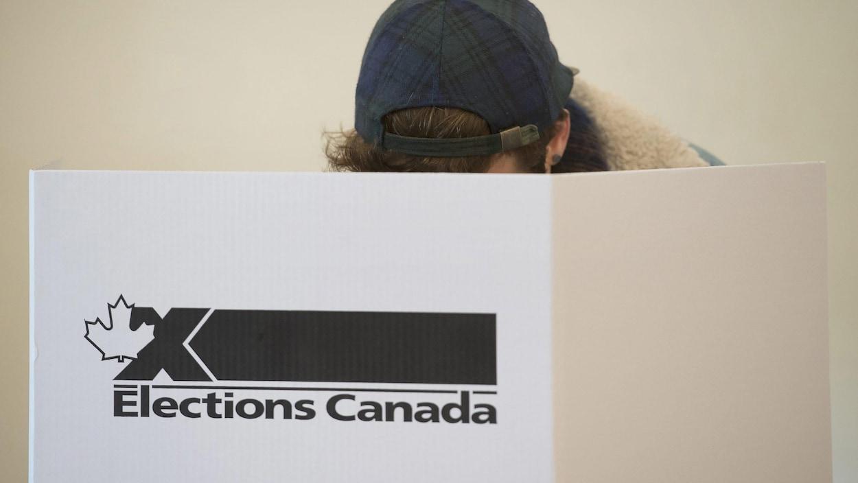 Une personne, dont le visage est caché par un carton où est inscrit le logo d'Élections Canada, en train de voter.