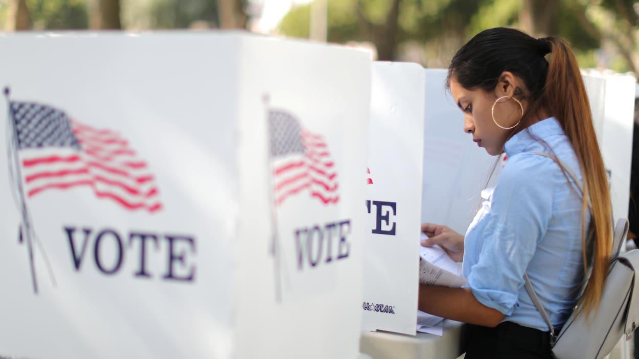 Une électrice consulte un document derrière un isoloir.