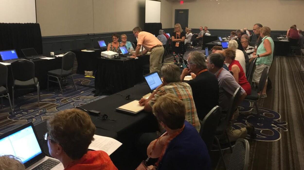 Des gens dans une salle assis devant des ordinateurs écoutent leur formateur