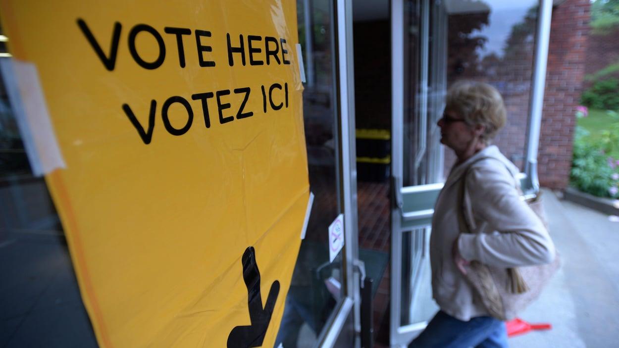 Un panneau est affiché sur la porte d'entrée du bureau de vote avec une inscription bilingue : Vote here, votez ici. Une femme entre par la porte.