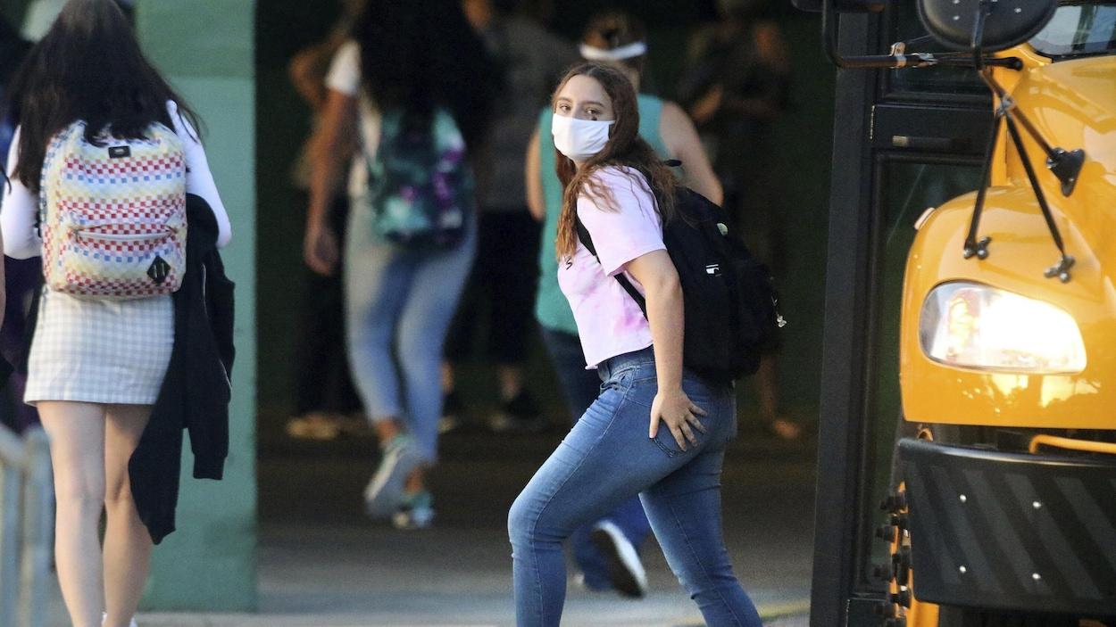 Une élève du secondaire qui porte un masque descend de l'autobus scolaire.