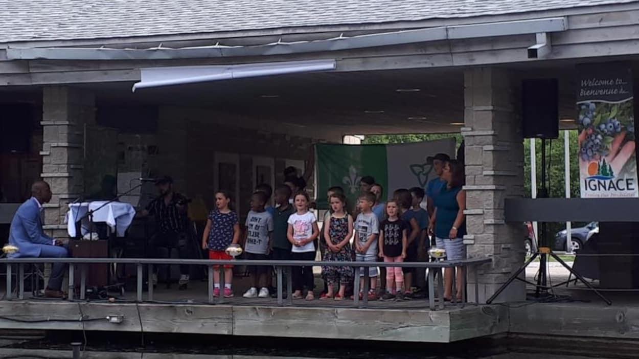 Un groupe d'enfant en train de chanter, accompagné par un pianiste, devant le drapeau franco-ontarien.