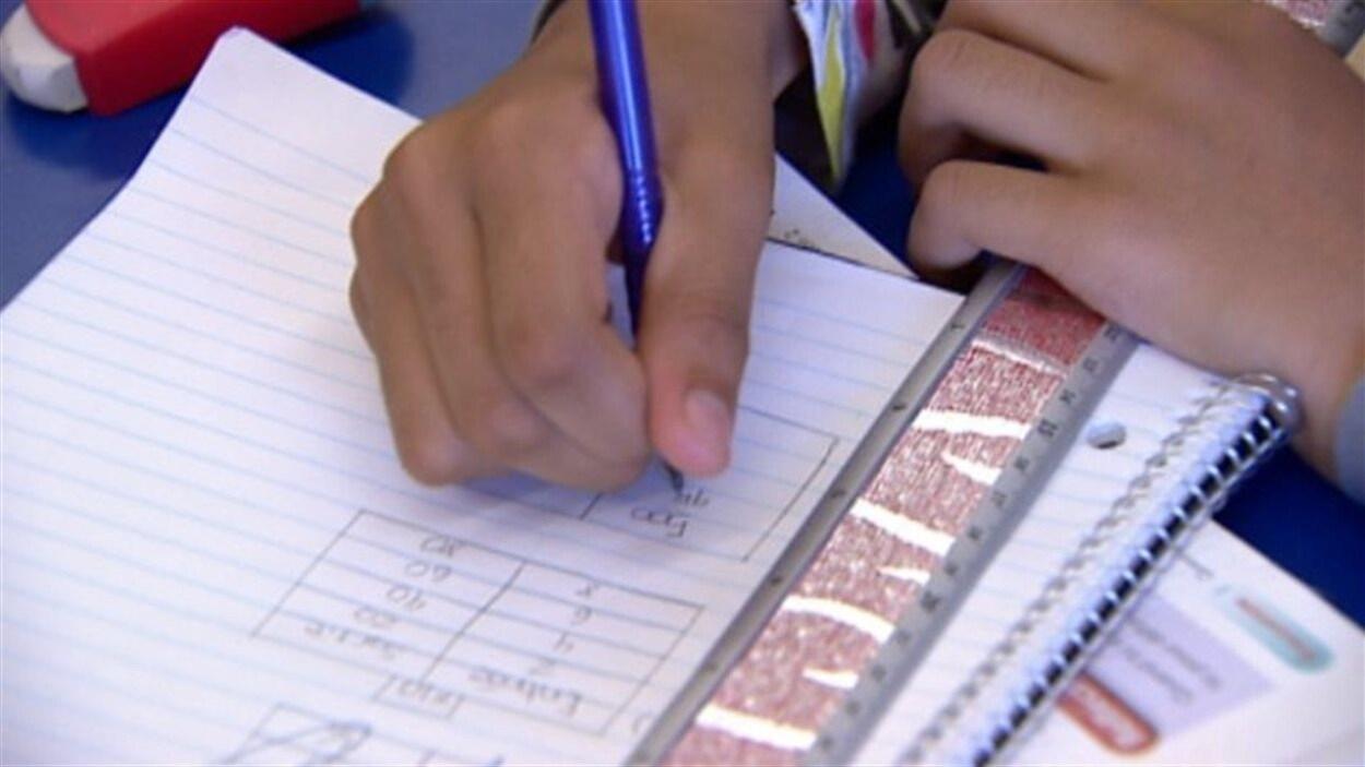 Un élève écrit dans un cahier, sur lequel une règle est déposée (archives).