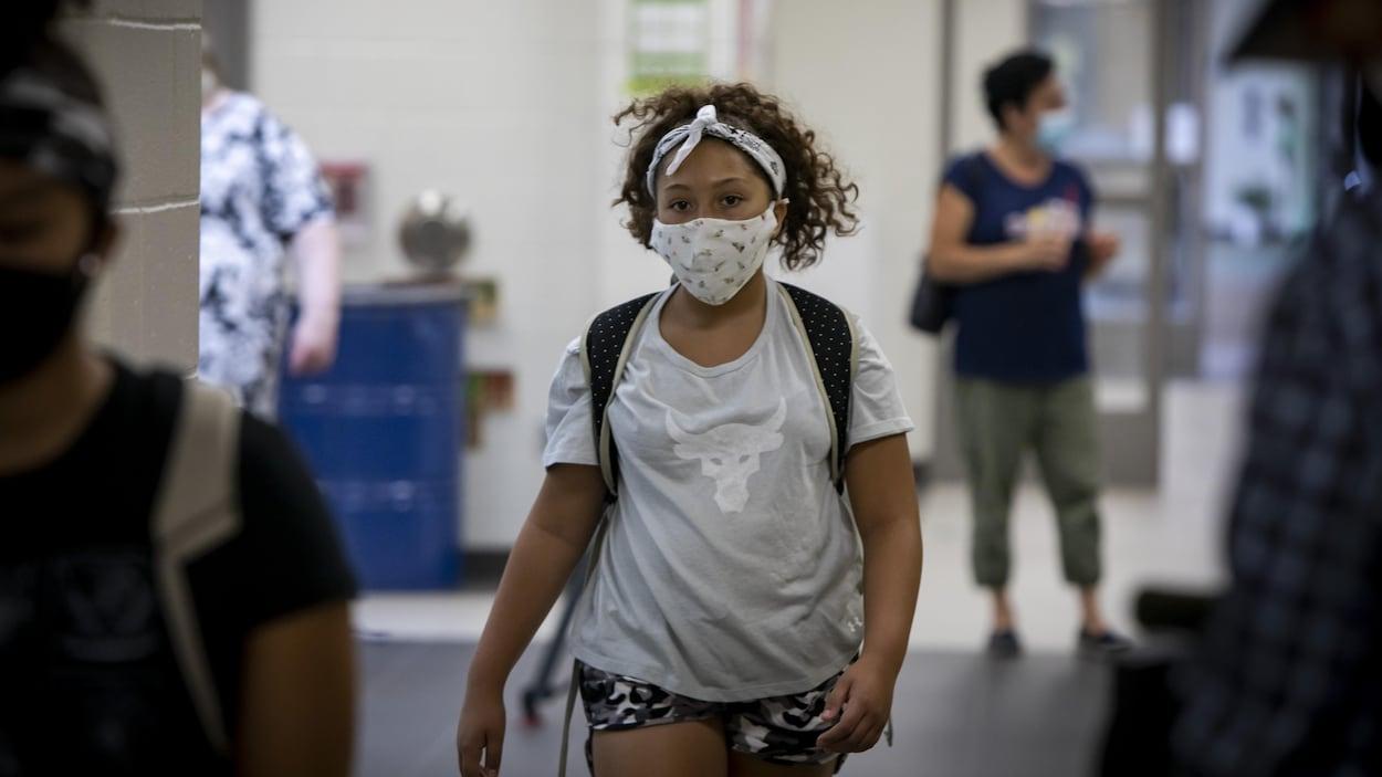 Une élève qui porte un masque arrive à l'école.