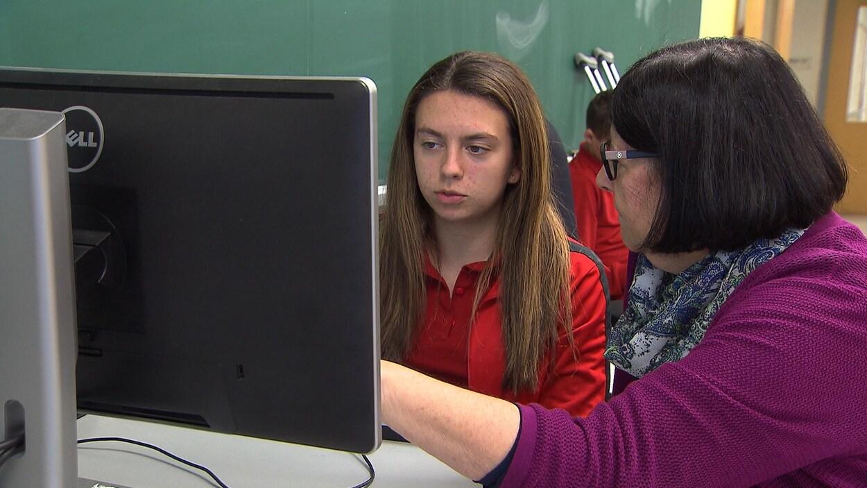 Une enseignante aide une élève qui écrit à l'ordinateur.