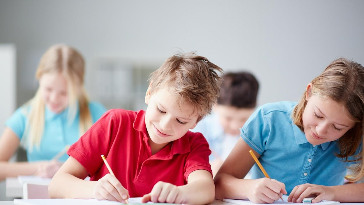Deux élèves écrivent sur leur cahier dans une salle de cours.