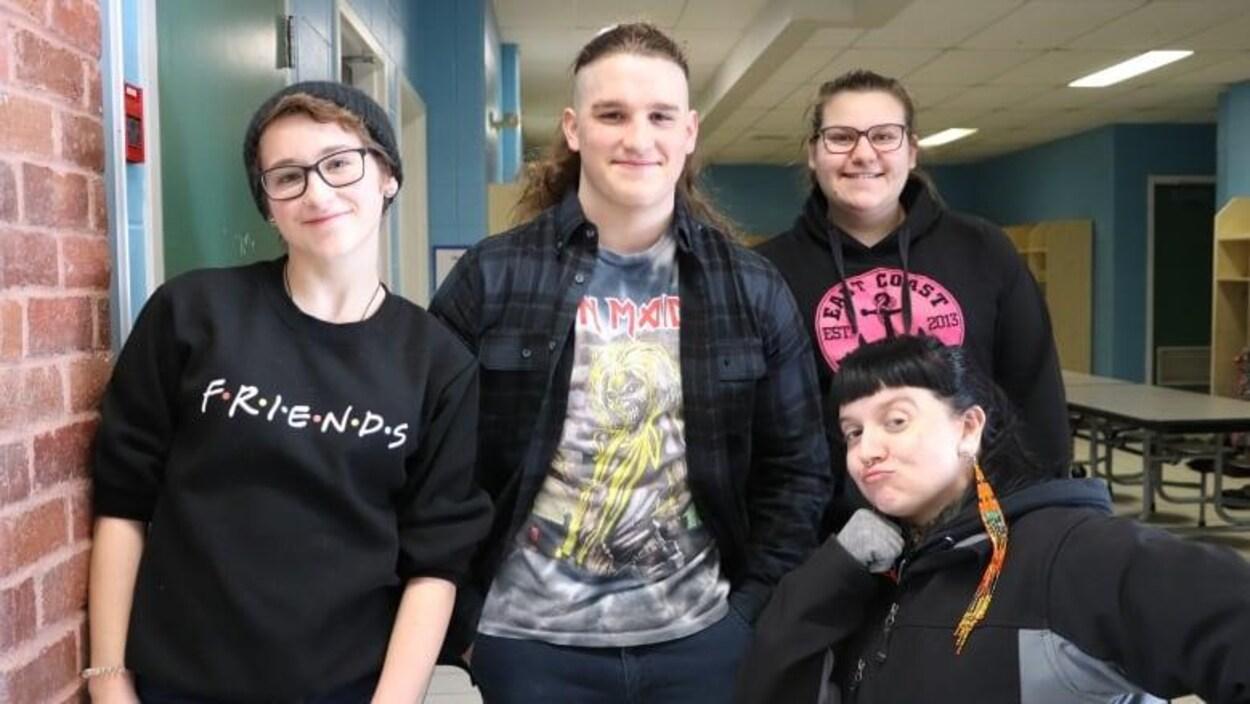 Trois élèves autochtones et l'artiste Dayna Danger prennent la pose dans une classe de l'école secondaire New Richmond High.