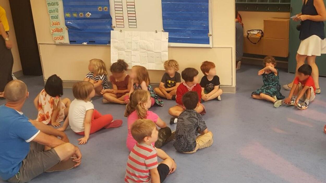 Des enfants assis par terre dans une classe de maternelle avec quelques parents en périphérie.