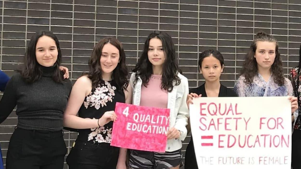 Des élèves tiennent une pancarte.
